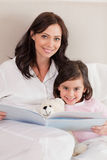 Portrait of a happy mother reading a story to her daughter Stock Image