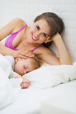 Portrait of happy mother and sleeping baby Stock Images