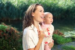 Portrait of a happy mother smiling with cute baby outdoors Stock Photos