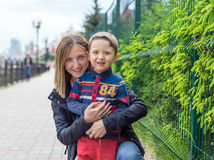 Portrait of happy mother and son on the street. Funny family making vacations and enjoying summer. Healthy lifestyle. Positive hum Stock Photos