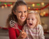 Portrait of happy mother and surprised baby looking on whisk Stock Photo