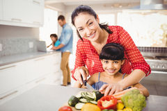 Portrait of happy mother teaching daughter to cut vegetables Royalty Free Stock Image
