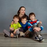 Portrait of happy mother and three sons, studio Royalty Free Stock Image