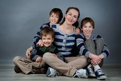 Portrait of happy mother and three sons, studio Stock Photo