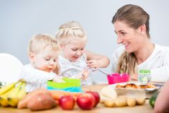 Portrait of a happy mother of two children sitting at table stock photo