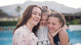Portrait of a happy mother with two daughters on the background of the pool. A happy mother with two daughters embraces and enjoy life. In the background there stock video footage