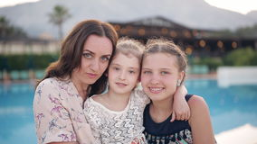 Portrait of a happy mother with two daughters on the background of the pool. A happy mother with two daughters embraces and enjoy life. In the background there stock footage