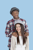 Portrait of happy multi ethnic couple over blue background Royalty Free Stock Images