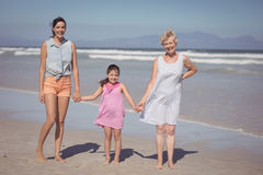Portrait of happy multi-generation family holding hands at beach. During sunny day Stock Photo