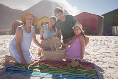 Portrait of happy multi-generation family by picnic blanket at beach stock photography