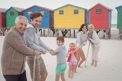 Portrait of happy multi-generation family playing tug of war. At beach Stock Image