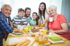 Portrait of happy multi-generation family sitting at breakfast table stock photo