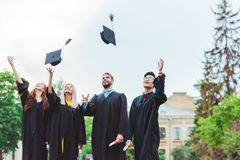 portrait of happy multicultural graduates with diplomas throwing caps up royalty free stock photos