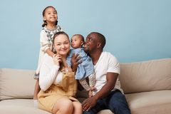Portrait of happy multiethnic family sitting on couch and having fun at home stock photography