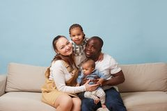 Portrait of happy multiethnic family sitting on couch and having fun at home stock image