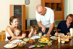 Portrait of happy multigeneration family  eating chicken with wi. Ne at home together Royalty Free Stock Photo