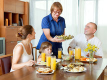 Portrait of happy multigeneration family  eating fish with juice. Portrait of happy multigeneration family  eating fish at home together Royalty Free Stock Photo