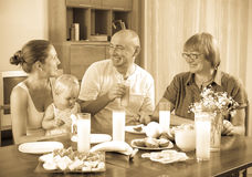 Portrait of happy multigeneration family  eating friuts and vege. Table at home together Stock Photos