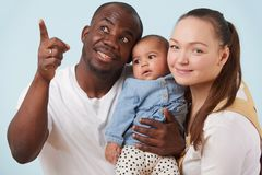 Portrait of happy multiracial family against pale blue background stock images