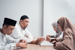 Muslim family reading quran or holy book of islam together. Portrait of happy muslim family reading quran or holy book of islam together royalty free stock photo
