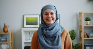 Portrait of happy Muslim lady in hijab smiling looking at camera in apartment. Portrait of happy Muslim lady in hijab smiling looking at camera indoors in stock video