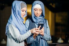 Young woman sitting and holding mobile phone. Portrait of happy muslim women using mobile phone while sitting on a couch Stock Images