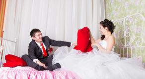 Portrait of happy newlywed couple fighting with pillows in bed.  Royalty Free Stock Image