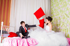 Portrait of happy newlywed couple fighting with pillows in bed.  Royalty Free Stock Photos