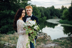 Portrait of a happy newlywed couple on the river bank Stock Images