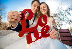 Portrait of happy newlyweds holding Love word sign Royalty Free Stock Photos