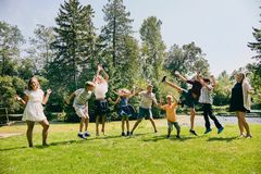 Happy children jumping or dancing in summer park. Portrait of happy nine children, friends or siblings, jumping or dancing in park during summer vacations Royalty Free Stock Photo