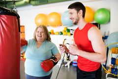 Happy Obese Woman Working Out with Coach. Portrait of happy obese women hitting punching bag and laughing while exercising in gym with personal fitness coach Royalty Free Stock Photography