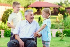 Portrait of happy old grandfather and cute children Stock Images