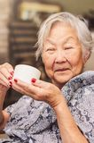 Portrait of a happy old lady japanese descendant seated comfor. Tably at home holding a cup of tea Stock Photography