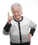 Portrait of a happy old woman pointing upwards Stock Images