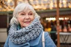 Glad senior lady walking in winter outdoor. Portrait of happy old woman standing on street and smiling. She is wearing warm coat and scarf Royalty Free Stock Image