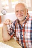 Portrait of happy older man smiling. At camera, holding glasses royalty free stock photo