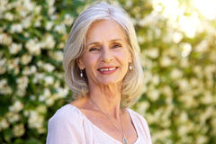 Portrait of happy older woman standing outside in summer Stock Images