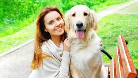 Portrait happy owner woman hugging Golden Retriever dog in city park. Portrait happy owner woman hugging her Golden Retriever dog in city park stock photo