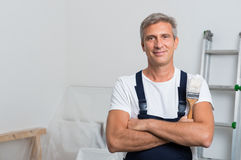 Portrait Of Happy Painter. Portrait Of Smiling Painter With Arm Crossed Holding Paintbrush At Home Royalty Free Stock Image