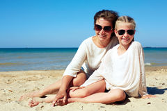Portrait of a happy parent and child resting on the beach Royalty Free Stock Images