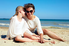 Portrait of a happy parent and child resting on the beach Stock Photo