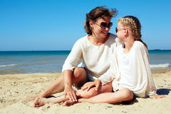 Portrait of a happy parent and child resting on the beach. Happy parent and child resting on the beach Royalty Free Stock Photo