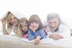Portrait of happy parents and children lying under bed cover stock image