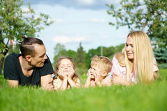 Portrait of happy parents with kids lying at the park Stock Photos