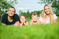 Portrait of happy parents with kids lying at the park royalty free stock photography
