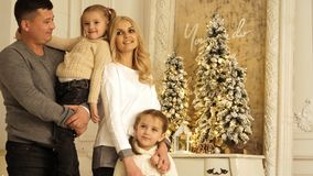 Portrait of happy parents with two daughters posing. Christmas photo session. stock photography