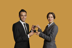 Portrait of happy partners holding winning trophy together Royalty Free Stock Image