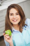 Portrait of happy patient in dental chair with green apple. stock photo