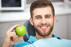Portrait of happy patient in dental chair with green apple. Stock Image